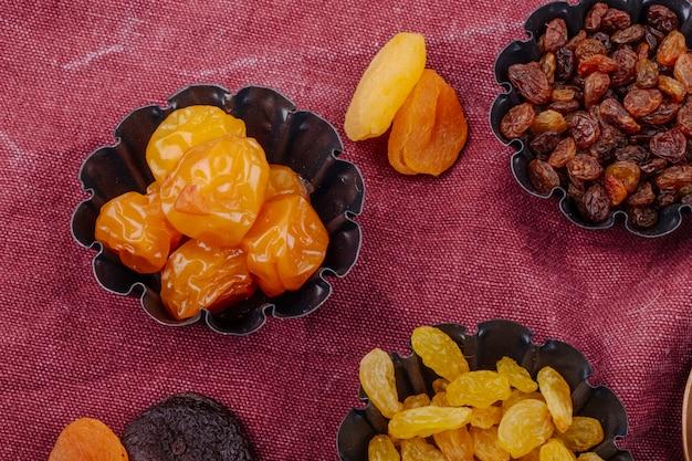 Vista lateral de frutas secas, ameixas de cereja, passas e damascos em latas de torta mini em fundo de textura de saco de carvão