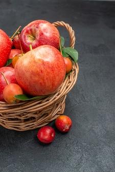 Vista lateral de frutas vermelhas-amarelas, cerejas e maçãs na cesta