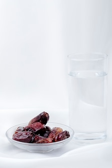 Vista lateral de frutos secos doces data em um pires com um copo de água no fundo branco