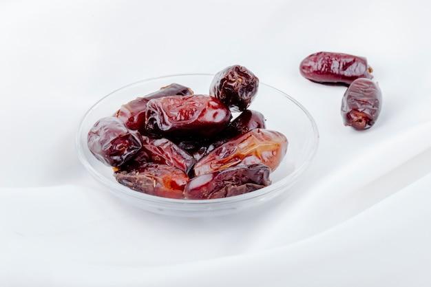 Vista lateral de frutos secos doces data em um pires em fundo branco