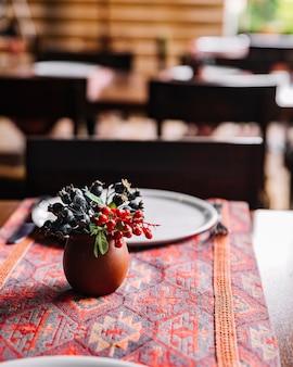 Vista lateral de frutos silvestres em uma panela de barro em cima da mesa