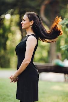 Vista lateral de garotas lindas com cabelos longos, vestindo elegantes vestidos pretos posando no parque