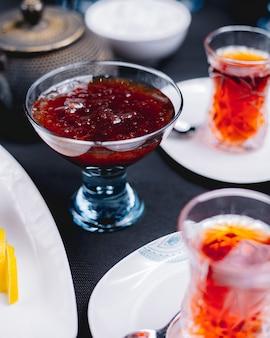 Vista lateral de geléia de morango caseira em um vaso de vidro servido com chá na superfície escura