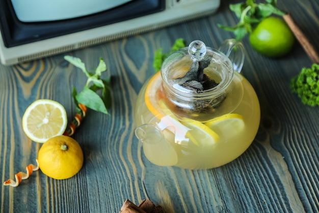 Vista lateral de gengibre chá limão hortelã água quente canela