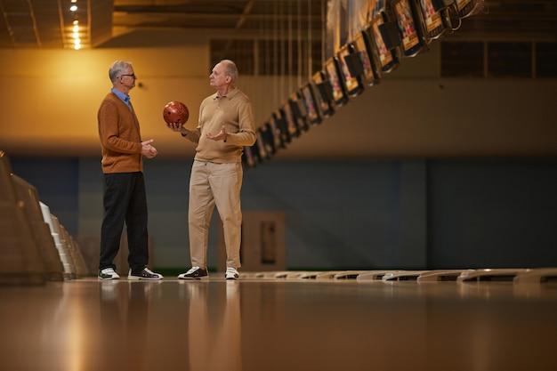 Vista lateral de grande angular para dois amigos sêniors jogando boliche juntos enquanto desfrutam de entretenimento ativo na pista de boliche, copie o espaço