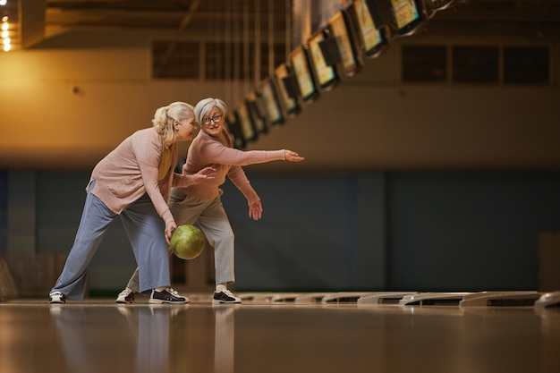 Vista lateral de grande angular para duas mulheres sêniors jogando boliche juntas enquanto desfrutam de entretenimento ativo na pista de boliche, copie o espaço
