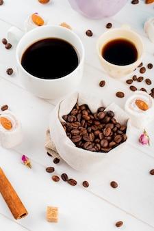 Vista lateral de grãos de café em um saco e xícaras de café sobre fundo branco