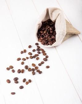 Vista lateral de grãos de café espalhados de um saco em fundo branco de madeira