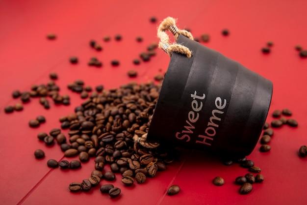 Vista lateral de grãos de café frescos caindo da cesta preta sobre fundo vermelho