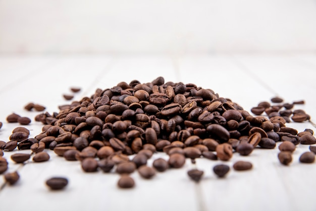Vista lateral de grãos de café frescos isolados em um fundo branco de madeira