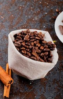 Vista lateral de grãos de café marrons em um saco e paus de canela em fundo preto