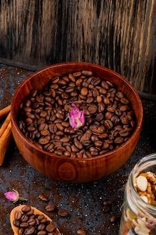 Vista lateral de grãos de café torrados em uma tigela de madeira em fundo preto