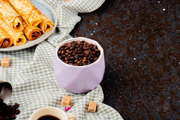 Vista lateral de grãos de café torrados em uma tigela e wafer rola com leite condensado em um prato com espaço de cópia