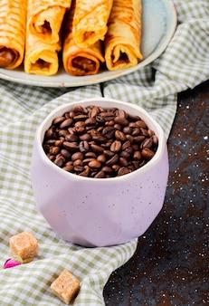 Vista lateral de grãos de café torrados em uma tigela e wafer rola com leite condensado em um prato