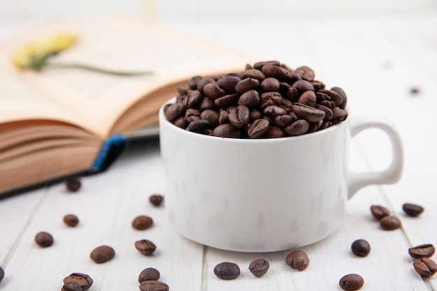 Vista lateral de grãos de café torrados frescos em um copo branco sobre fundo branco de madeira