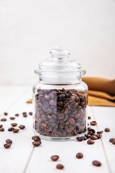Vista lateral de grãos de café torrados frescos em uma jarra de vidro com fundo branco de madeira