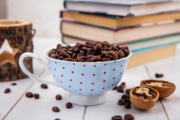 Vista lateral de grãos de café torrados frescos em uma xícara de bolinhas com nozes em um fundo branco de madeira