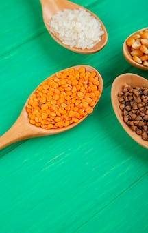Vista lateral de grãos de cereais e sementes em colheres de madeira grãos de arroz trigo sarraceno e lentilhas vermelhas na mesa verde