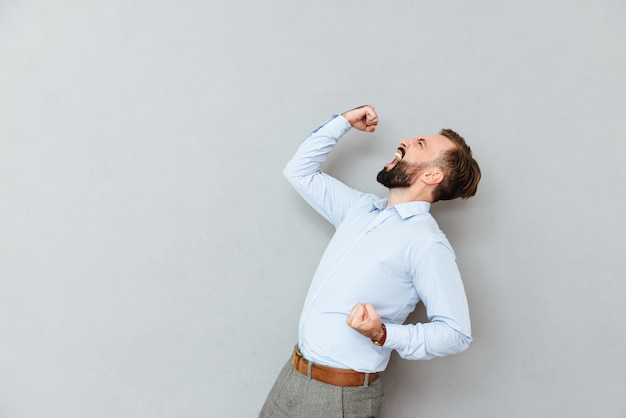 Vista lateral de gritar feliz homem barbudo em roupas de negócios