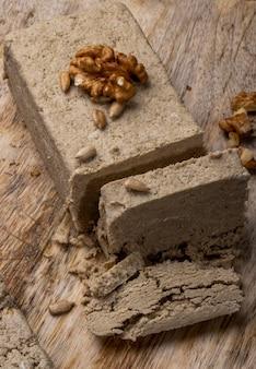 Vista lateral de halva com sementes de girassol e nozes em uma placa de madeira