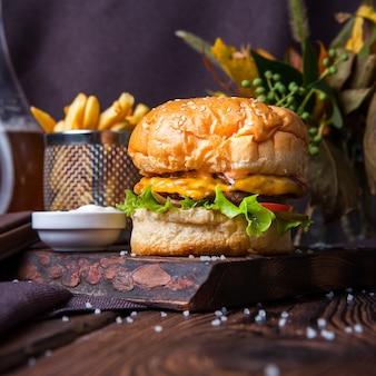 Vista lateral de hambúrguer e batatas fritas em um fundo preto e madeira com decorações