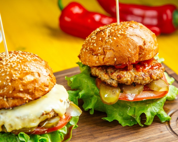 Vista lateral de hambúrgueres com costeleta de frango derretido queijo tomate e picles na placa de madeira