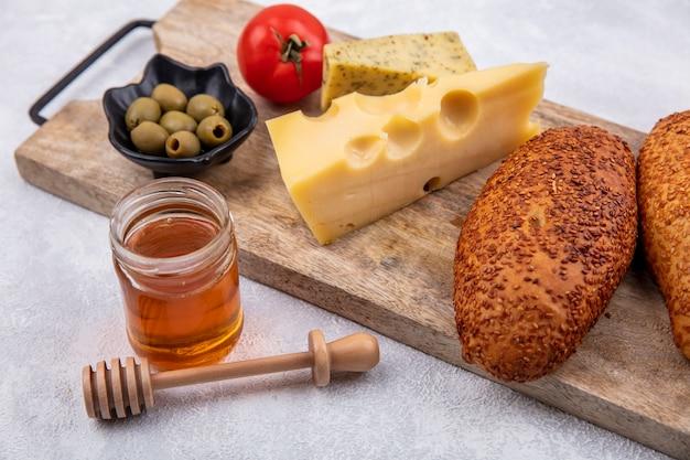 Vista lateral de hambúrgueres de gergelim em uma placa de cozinha de madeira com azeitonas verdes em uma tigela preta e queijo com mel em um fundo branco