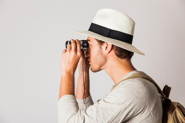 Vista lateral de hipster homem com binóculos