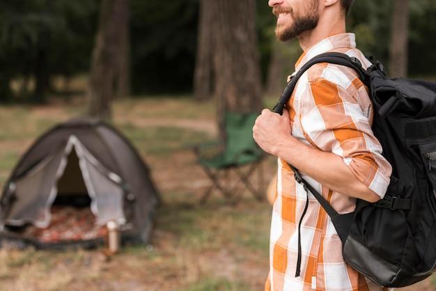 Vista lateral de homem com mochila e acampamento com barraca