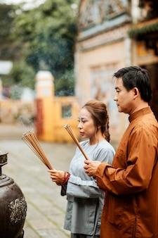 Vista lateral de homem e mulher com incenso no templo