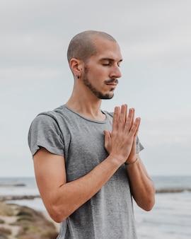Vista lateral de homem fazendo ioga ao ar livre