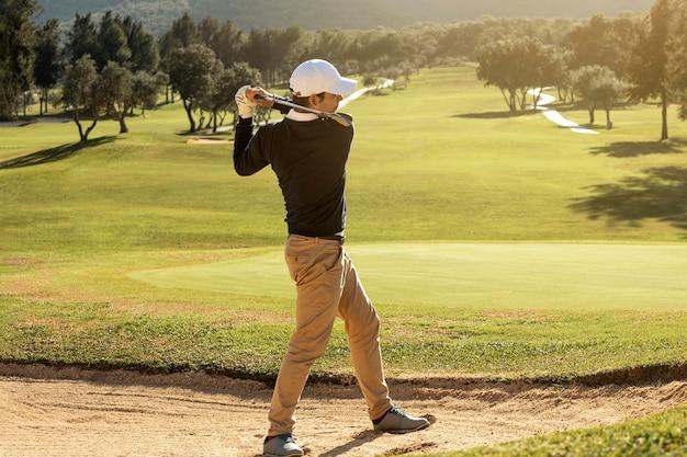 Vista lateral de homem jogando golfe com o taco