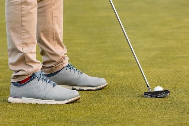 Vista lateral de homem jogando golfe com taco e bola