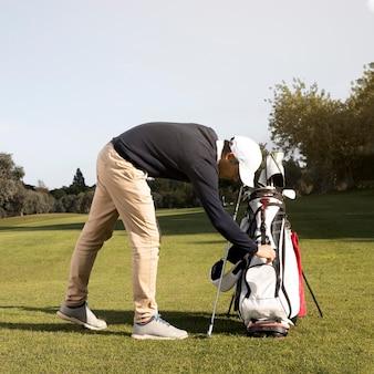 Vista lateral de homem jogando golfe no campo
