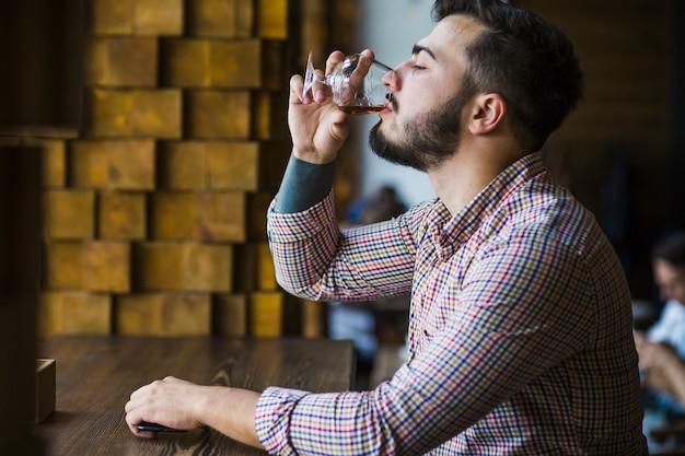 Vista lateral, de, homem jovem, desfrutando, bebida