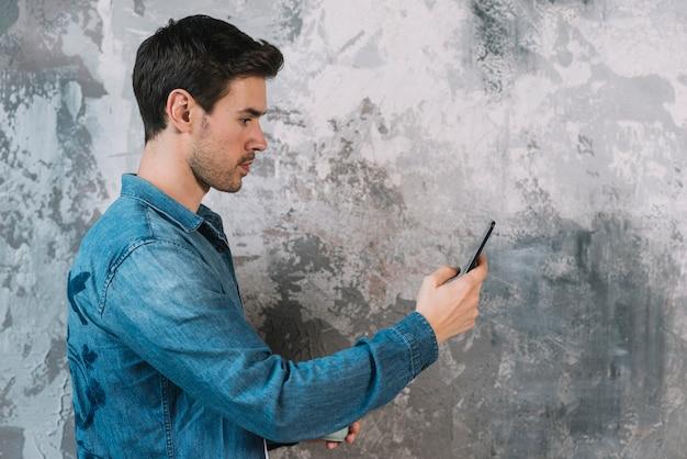 Vista lateral, de, homem jovem, ficar, frente, grunge, parede, usando, cellphone