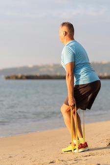 Vista lateral de homem malhando com corda elástica na praia
