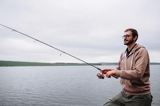 Vista lateral, de, homem, pesca, com, vara, ligado, lago