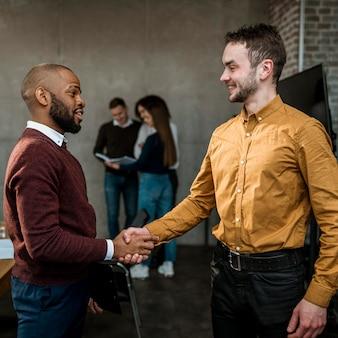 Vista lateral de homens apertando a mão em acordo após uma reunião