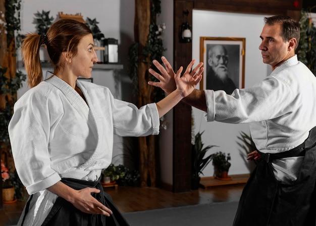 Vista lateral de instrutor de artes marciais praticando com estagiária