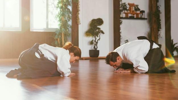 Vista lateral de instrutores de artes marciais se saudando antes do treino