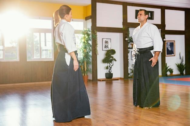 Vista lateral de instrutores de artes marciais treinando na sala de prática