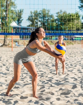 Vista lateral de jogadoras de vôlei jogando na praia