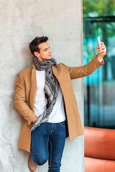 Vista lateral, de, jovem, homem elegante, inclinar-se, um, parede, ao ar livre, desgastar, roupa denim, enquanto, levando, um, selfie, em, dia ensolarado