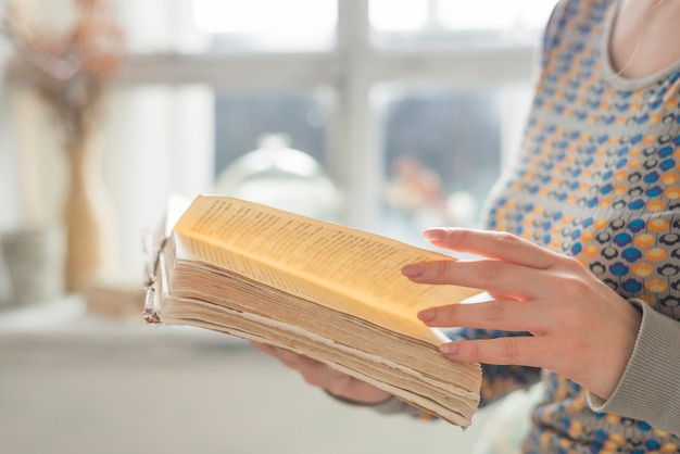 Vista lateral, de, jovem, mulher, mão, girar, a, páginas, de, livro