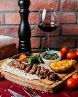 Vista lateral de kebab de cordeiro com ervas e legumes em uma placa de madeira