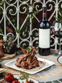 Vista lateral de kebab de costela de cordeiro no prato servido com uma garrafa de vinho tinto