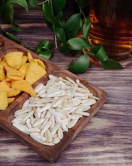 Vista lateral de lanches de cerveja sementes de girassol e batatas fritas em uma bandeja de madeira com uma caneca de cerveja no rústico