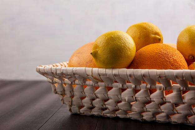 Vista lateral de laranjas em uma cesta com limões e toranjas