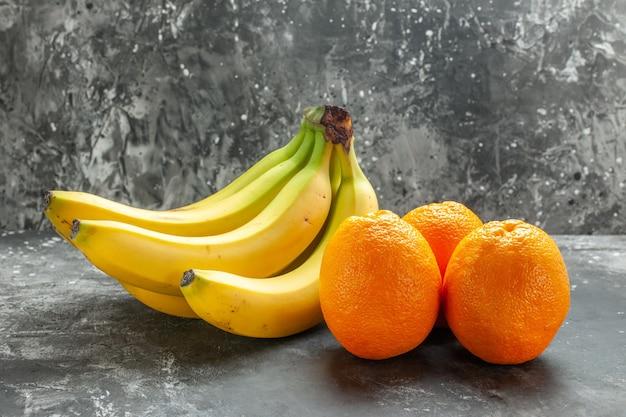 Vista lateral de laranjas frescas e bananas orgânicas naturais com fundo escuro